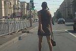 Frau geht ohne zu gucken über eine Straße