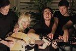 5 Leute spielen auf einer Gitarre