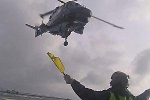 Hubschrauber landet auf Schiff bei rauer See