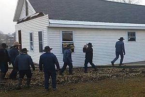 80 Menschen tragen ein Haus