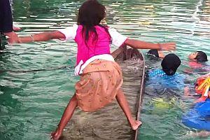 Mädchen entleert vollgelaufenes Kanu