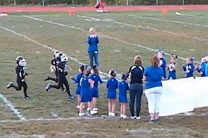 Football-Kinder laufen durch ein Banner