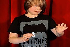 Junge zeigt seinen Zaubertrick mit Münzen