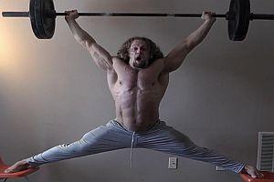 Muskelprotz macht Spagat auf Stühlen