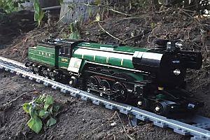 Lego-Eisenbahn fährt durch Haus und Garten
