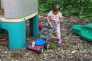 Mädchen mit einem Rasenmäher