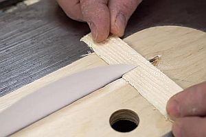 Mit Papier ein Stück Holz zersägen