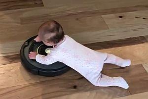 Baby fährt mit Saugroboter