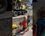 Baggerfahrer befüllt Spielzeug-Lastwagen